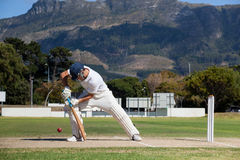 Full length of batsman playing cricket on field against mountain. During sunny day royalty free stock image
