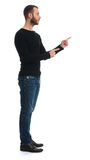 Full length of bearded guy pointing finger to something Stock Image