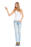Full length of beautiful blond woman pointing at copy space over white background Royalty Free Stock Image