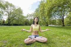 Full length of beautiful fit woman performing yoga at park Stock Photography