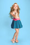 Full length of beautiful little girl in dress standing and posing over blue background royalty free stock photos