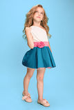 Full length of beautiful little girl in dress standing and posing over blue background Stock Image