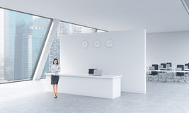 A full length of a beautiful receptionist in a bright modern roof loft office with panoramic Singapore view. The concept of luxury Royalty Free Stock Image