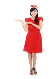 Full length of beautiful woman in christmas santa hat showing co Stock Photography