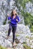 Full length of beautiful woman holding hiking pole while climbin Royalty Free Stock Photo