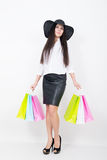 Full length of a beautiful young asian lady in a white blouse and black leather skirt holding colorful bags. Girl goes Stock Images