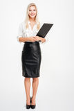 Full length of beautiful young businesswoman standing and holding clipboard Royalty Free Stock Photo
