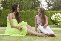 Full length of beautiful young female friends conversing in park Stock Photo