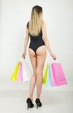 Full length of a beautiful young lady in a bathing suit, big black hat on high heels, holding colorful bags. Girl goes Royalty Free Stock Images