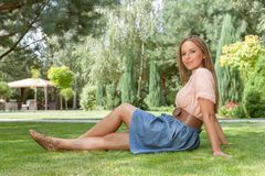 Full length of beautiful young woman looking away while relaxing on grass in park Royalty Free Stock Images
