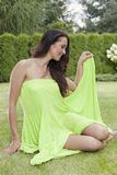 Full length of beautiful young woman in sundress sitting at park Royalty Free Stock Photography