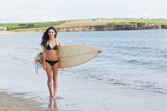 Full length of bikini woman holding surfboard at beach Stock Image