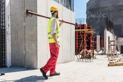 Blue-collar worker carrying a heavy metallic bar during work. Full length of a blue-collar worker wearing safety equipment, while carrying a heavy metallic bar royalty free stock photo