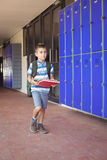 Full length of boy carrying books in corridor. At school Royalty Free Stock Image