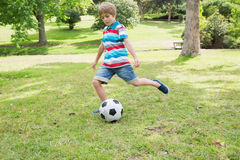 Full length of a boy kicking ball at park Royalty Free Stock Photos