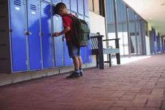 Full length of boy leaning on lockers in corridor royalty free stock image