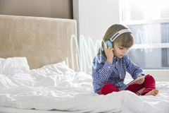 Full length of boy listening music through headphones on bed Royalty Free Stock Images