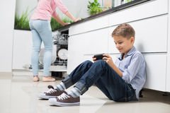Full length of boy using hand-held video game with mother in background at kitchen royalty free stock photography