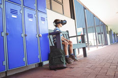 Full length of boy using virtual reality glasses while sitting on bench. By lockers in corridor at school Stock Photography