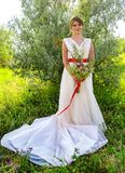 Bride with a bouquet in a white dress with a red ribbon near a tree in the summer Royalty Free Stock Photography