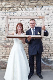Full length of bride and groom looking through portrait frame Stock Photo