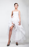 Full-length bride in a wedding dress and bridal hairdo, lifted the hem of her dress. provocation playful bride.  Stock Photos
