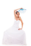 Full length bride in wedding gown holds fan isolated Royalty Free Stock Image