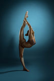 Full length of bronzed gymnast performs  at studio. Full length side view shot of flexible slim woman with athletic bronzed body performing at studio, copy space