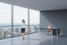 Full-length of brunette business lady in a workplace at modern corner panoramic office in New York, Manhattan. A concept of stock photos