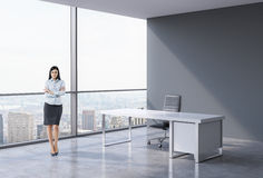 Full-length of a brunette business woman in a workplace at modern panoramic office in New York, Manhattan. A concept of financial Stock Images