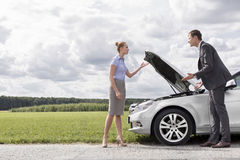 Full length of business couple arguing by broken car at countryside Stock Images
