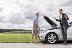 Full length of business couple having argument by broken car at countryside Stock Image