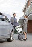 Full-length of business couple with luggage outside hotel Stock Photography