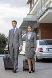 Full-length of business couple with luggage walking outside hotel Royalty Free Stock Images