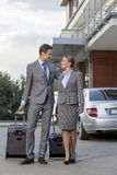 Full-length of business couple walking with luggage outside hotel Royalty Free Stock Image