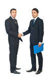 Full length of business men handshake. Full length of two business men shaking hands and one of them holding a folder with contract isolated on white background royalty free stock photo