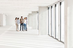Full length of business people discussing in empty office Royalty Free Stock Image