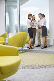 Full length of business people discussing in lobby Stock Images