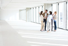 Full length of business people having discussion in empty office space Stock Photography