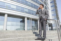 Full length businessman answering cell phone while standing on steps outside office Royalty Free Stock Images