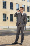 Full length of businessman conversing on cell phone against office building Royalty Free Stock Images