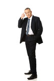 Full length businessman gesturing idiot sign Royalty Free Stock Image
