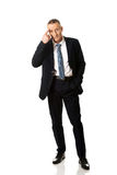 Full length businessman gesturing idiot sign Stock Photo
