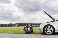 Full length of businessman with hands on head sitting by broken down car at countryside Stock Photos