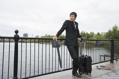 Full length of businessman with luggage leaning on railing along river Royalty Free Stock Photography