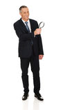 Full length businessman with a magnifying glass Royalty Free Stock Photography