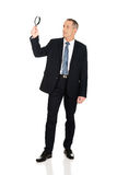 Full length businessman with a magnifying glass Stock Photo