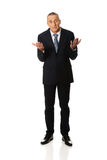 Full length businessman making undecided gesture Royalty Free Stock Images
