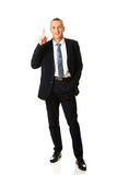 Full length businessman pointing upwards Stock Photos