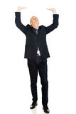 Full length businessman pushing invisible ceiling Royalty Free Stock Photos